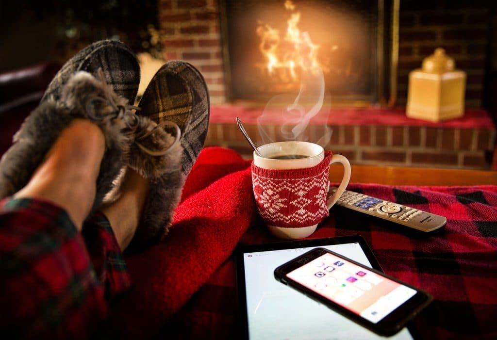 Pés com pantufas repousando em cima de uma mesa, com uma xícara quente ao lado, um tablet e um celular. Ao fundo, uma lareira acesa.