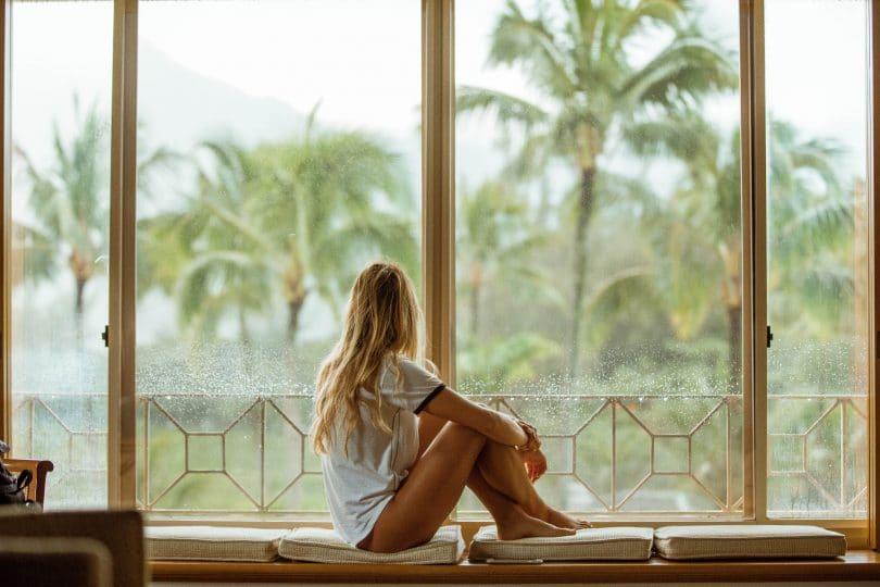 Mulher sentada em uma janela.
