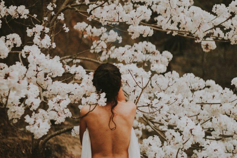 Mulher entre galhos de uma árvore florida.