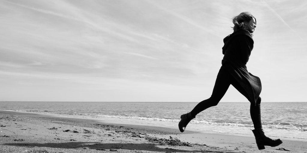 Mulher vestindo uma roupa preta e um coturno preto. Ela está correndo na areia da praia e parece que está meio desesperada.