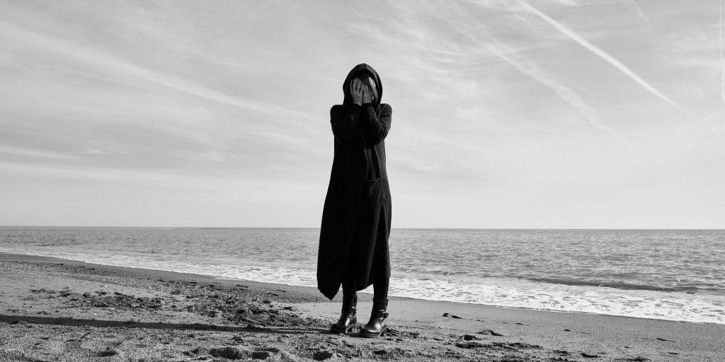 Mulher vestindo um longo casado com capuz na cor preta. Ela está com as duas mãos sobre o seu rosto. No fundo aparece o mar. A imagem é preto e branco.