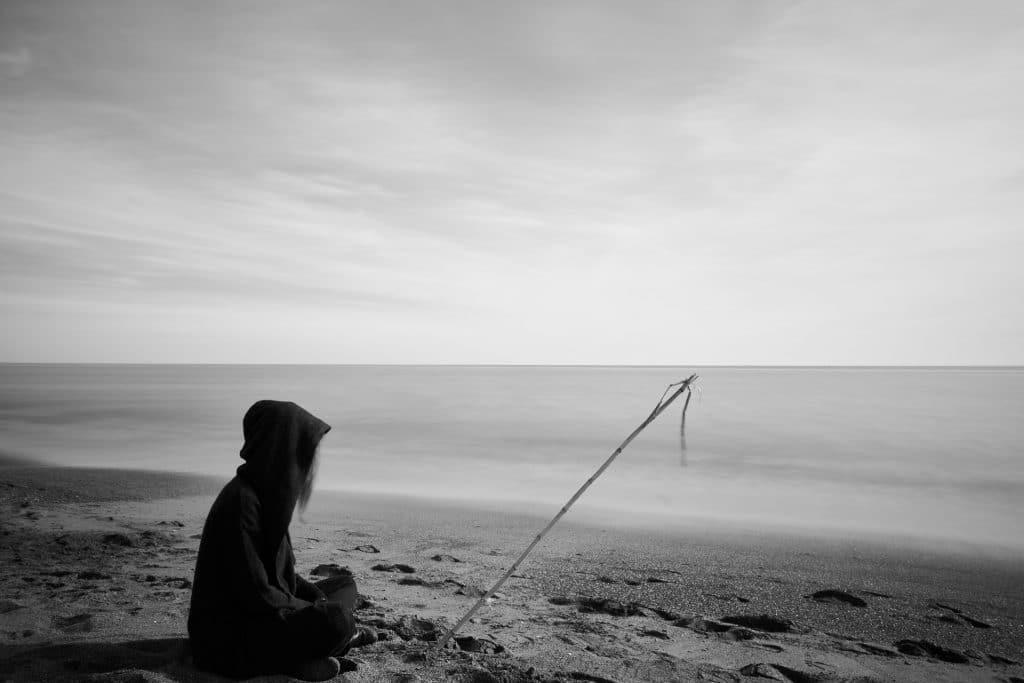 Imagem de uma mulher vestindo uma roupa preta. Ela está com um capuz preto sobre a cabeça e sentada na areia olhando para o mar. Ela está triste. A imagem é preto e branco.