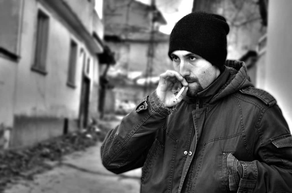Imagem em preto e branco de um homem com barba cerrada. Ele está agasalhado com uma jaqueta de frio e uma touca de lã preta. Ele está em um beco de rua e fuma um cigarro.