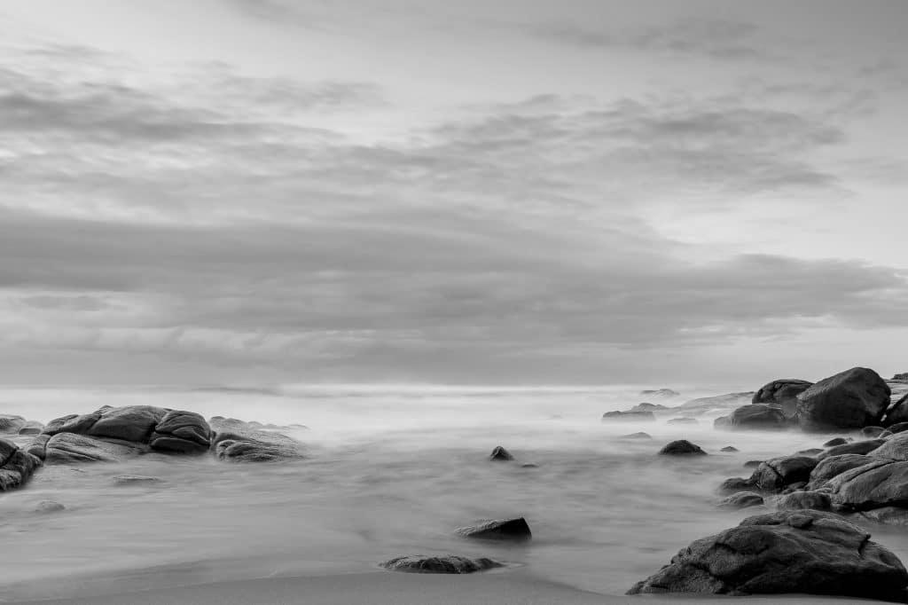Imagem do mar de leite e junto algumas rochas e pedras gigantes.