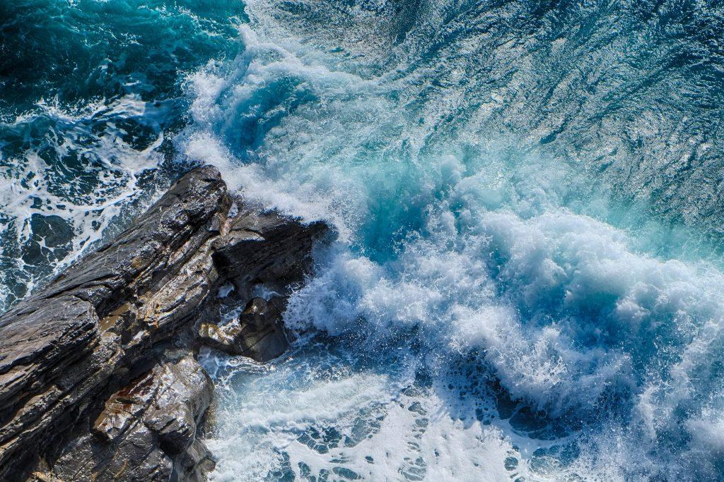 Imagem de uma praia azul. As ondas estão quebrando em uma pedra rochosa.