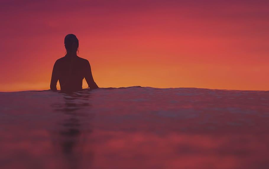 Silhueta de mulher no mar, de costas para a câmera, com a água na altura de sua cintura. O céu está alaranjado e escuro.