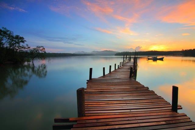 Ponte de madeira no meio de rio com paisagem ao fundo