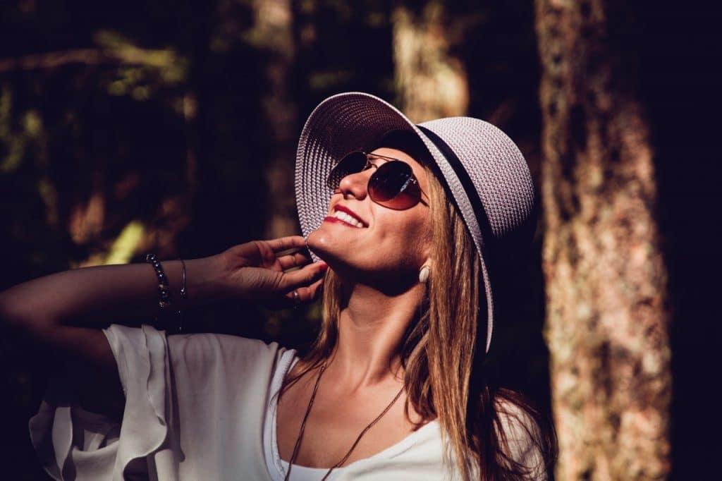 Mulher usando chapéu e óculos de sol, com a mão direita encostando em seu rosto, sorrindo e olhando para o alto em uma floresta.