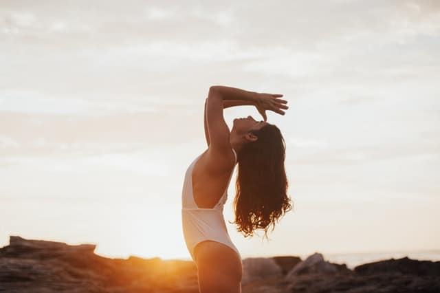 Mulher olhando para o alto com mãos em frente ao rosto com sol refletindo ao fundo
