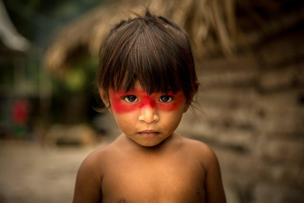 Criança indígena olhando para frente com tristeza