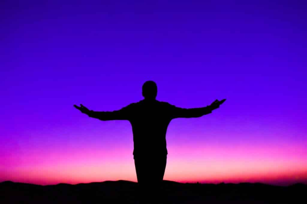 Silhueta de um homem de costas, de braços abertos, em frente ao pôr do sol.