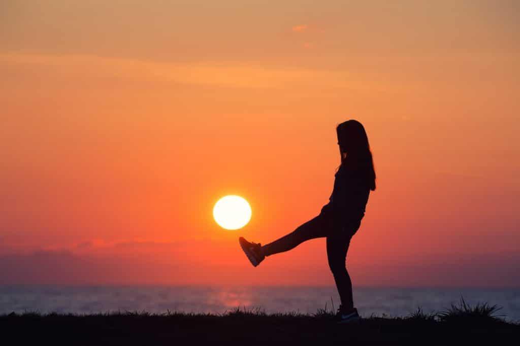 Silhueta de mulher com pôr-do-sol ao fundo como se ela estivesse chutando-o