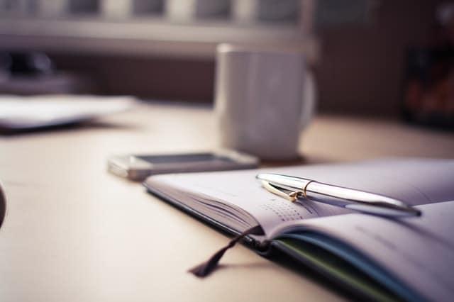 Mesa com agenda, caneta, celular e xícara visto de lado