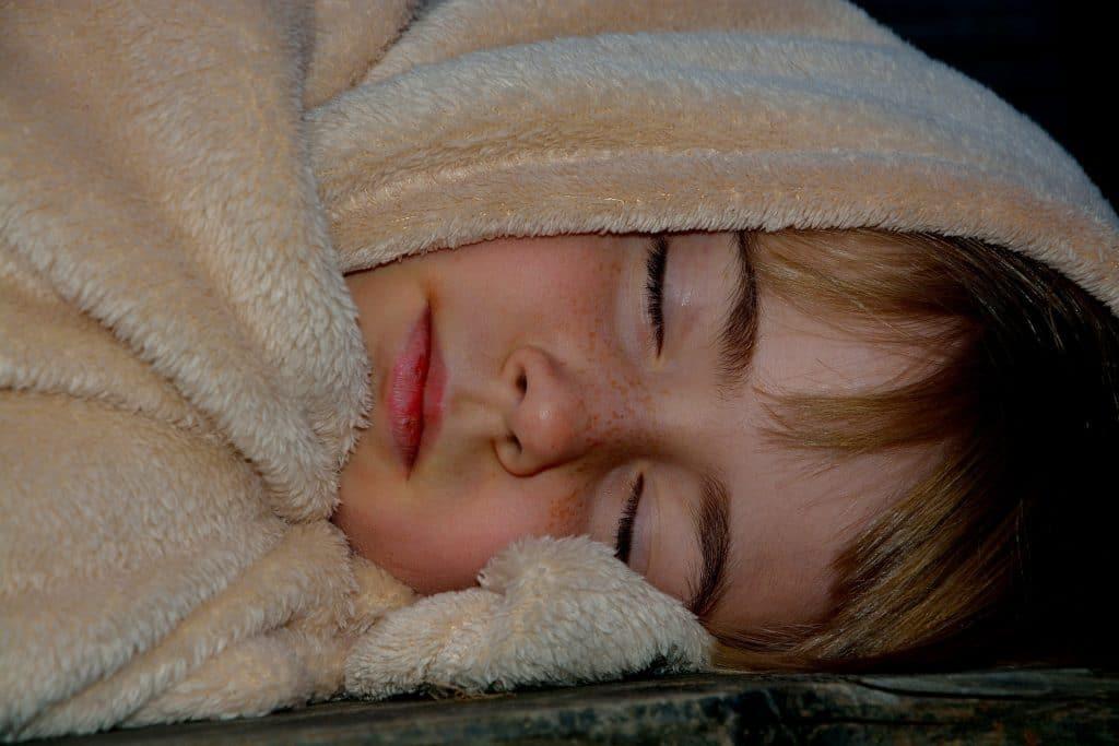 Imagem mde uma criança dormindo. Ela está envolta de uma coberta de pelinho na cor bege.