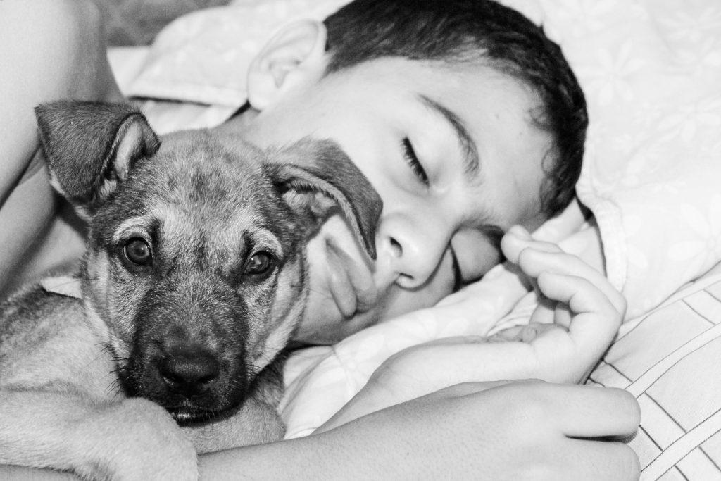Imagem de uma criança dormindo abraçada ao seu cachorro que está acordado e atento.