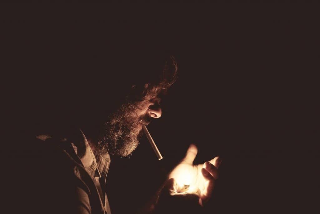 Imagem de um homem barbuda com um cigarro na boca e acendendo o isqueiro com as outras mãos.