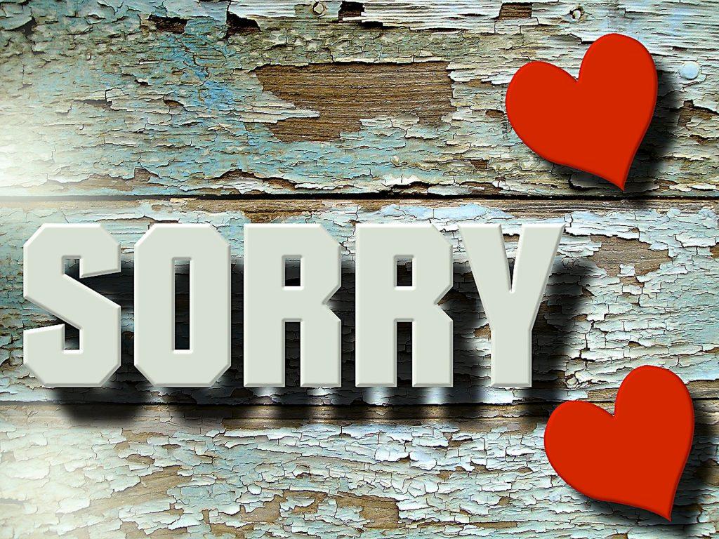 Imagem de uma parede de madeira descascada. Nela está escrita a palavra desculpe em inglês - Sorry - em letras grandes na cor branca. Ao lado da palavra temos dois corações vermelhos.