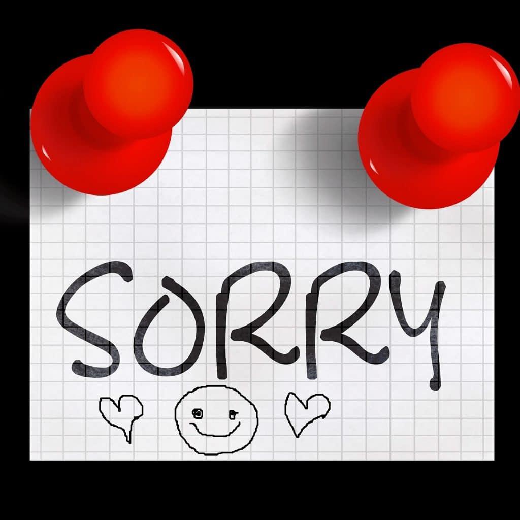Imagem de um lembrete fixadoo em um quadro negro com percevejos vermelhos. No bilhete está escrita a palavra desculpe em inglês: sorry e o desenho de uma carinha feliz e dois corações.