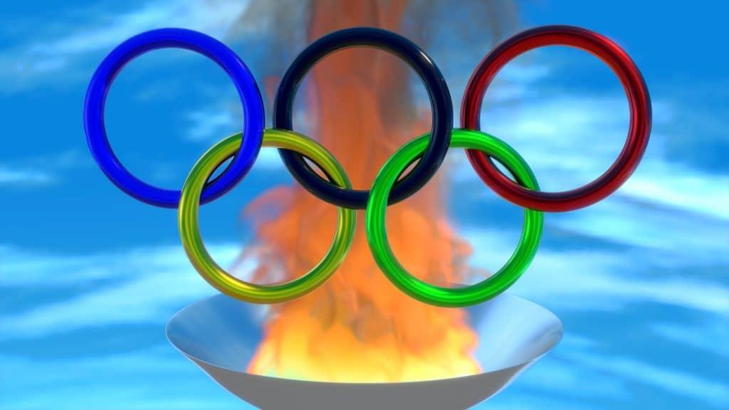 Imagem dos anéis do símbolo das olimpíadas nas cores azul claro, escuro, vermelho, verde e amarelo. Os aros estão sobre uma tocha de fogo.