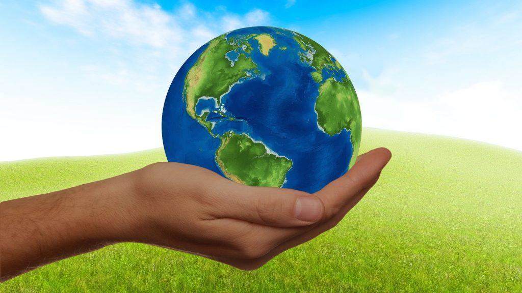 Imagem de uma mão masculina segurando o globo terrestre. Ao fundo um gramado bem verdinho.