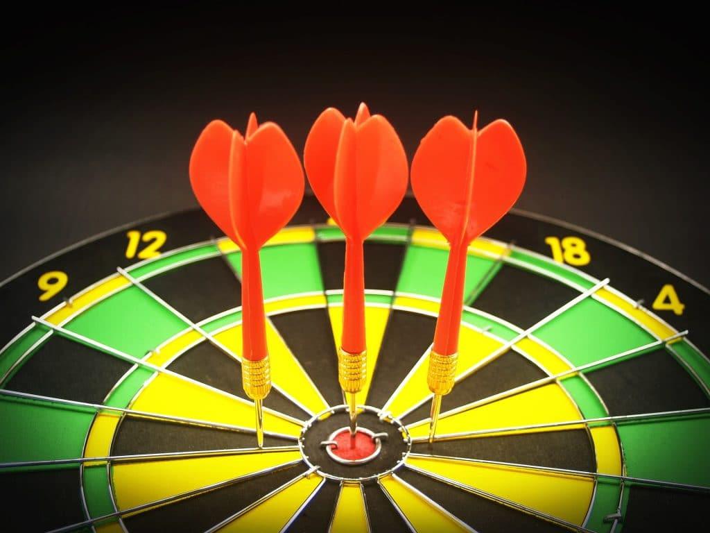 Imagem de uma tábua de tiro ao alvo com três flechas sendo que uma acertou o alvo e as outras duas estão próximas ao alvo.