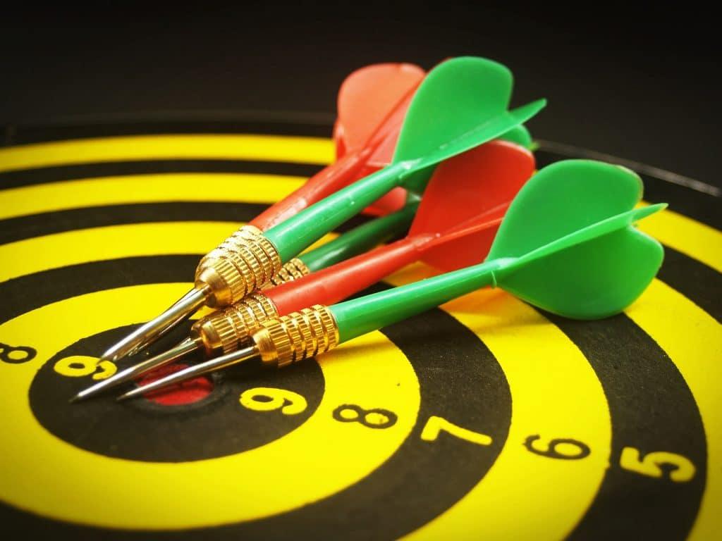 Tábua de tiro ao alvo e sobre ela quatro flechas nas cores verde e vermelho.