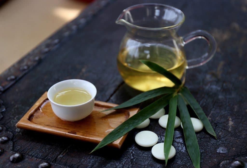 Chá de alecrim servido em uma jarra de vidro e em uma caneca de porcelana branca.