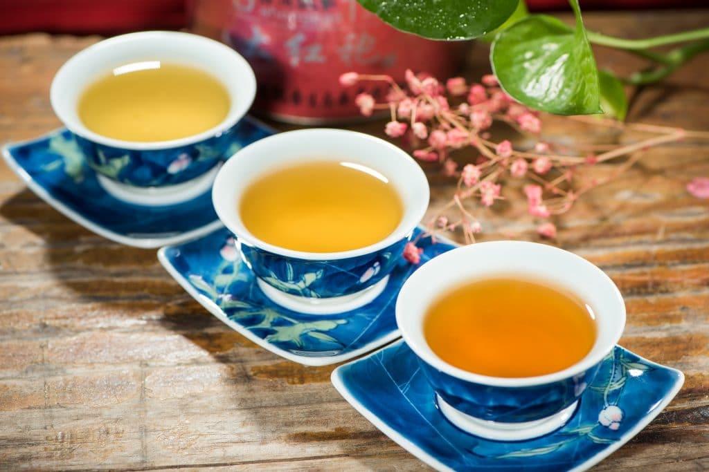 Chás a serem servidos no ritual do chá das cinco. A bebida está sendo servida em xícaras de porcelana nas cores azul e branco.