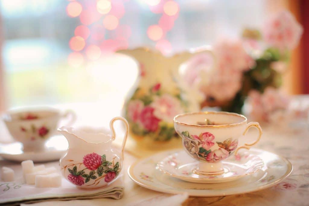 Mesa posta para celebrar a cerimônia do chá que será servido em porcelanas decoradas com flores rosas.