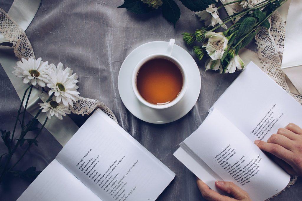 Imagem de uma xícara de porcelana branca cheia de chá. Ela está sobre uma mesa forrada com uma toalha cinza decorada com margaridas. Temos ainda dois livros abertos, sendo um deles manuseado por mãos de uma mulher.