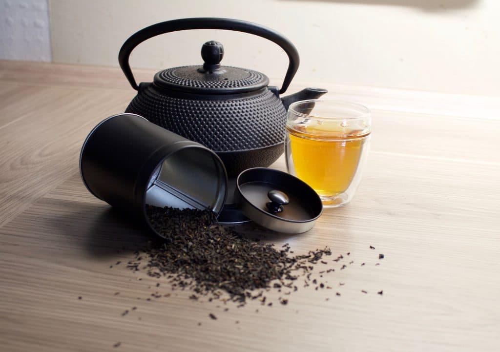 Imagem de chá preto em grãos dentro de um pote de alumínio. Ao lado uma chaleira e um copo com a bebida já preparada.