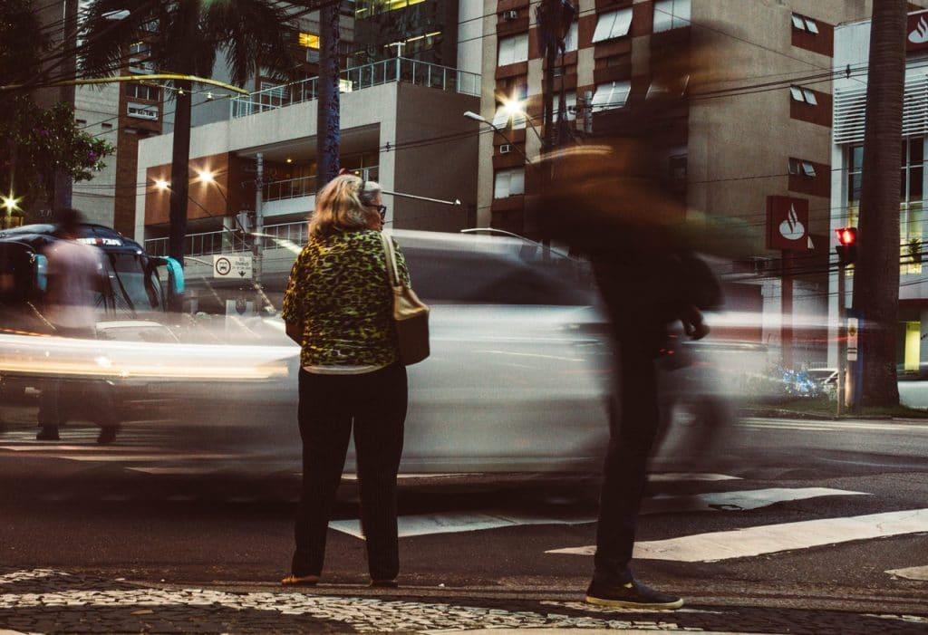 Senhora parada na calçada, de costas, enquanto carros e pessoas passam rapidamente pela rua.