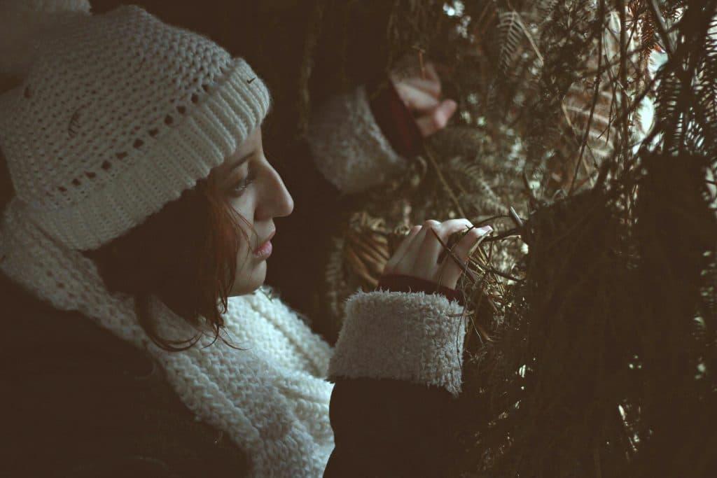 Mulher com roupas de frio olhando entre galhos