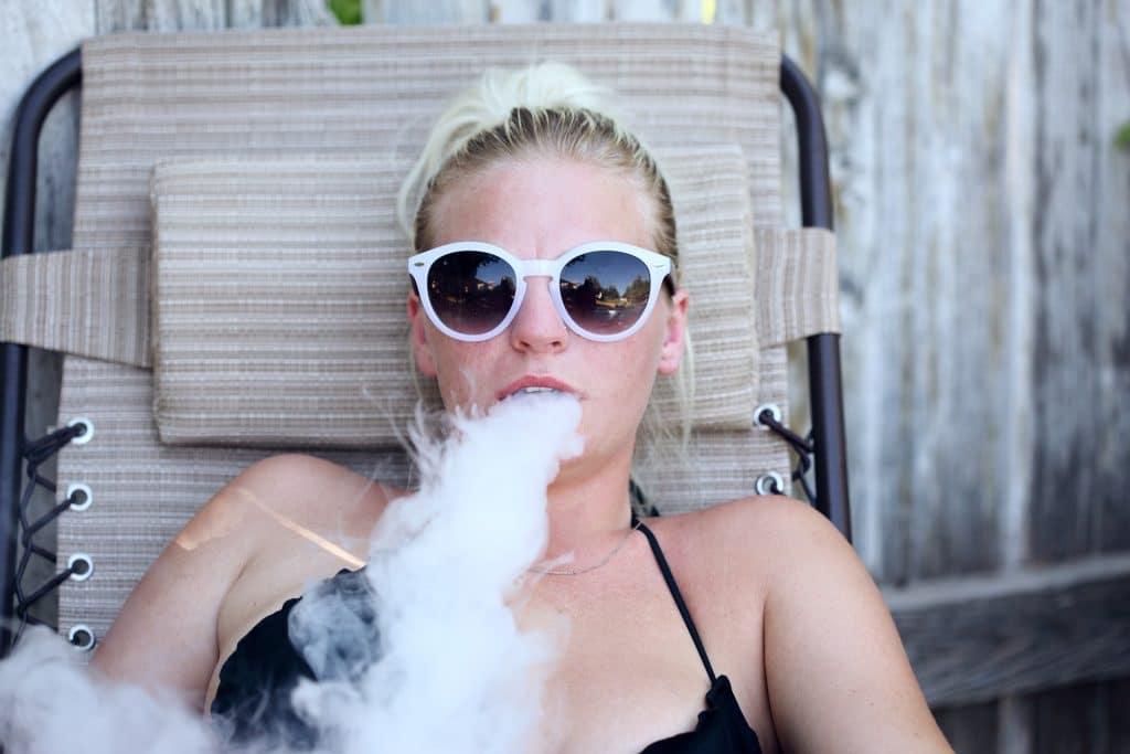 Mulher loira com cabelos presos. Ela está sentada em uma cadeira de praia de tecido marrom. Ela usa óculos de sol com armação branca. Ela fuma e solta muita fumaça.