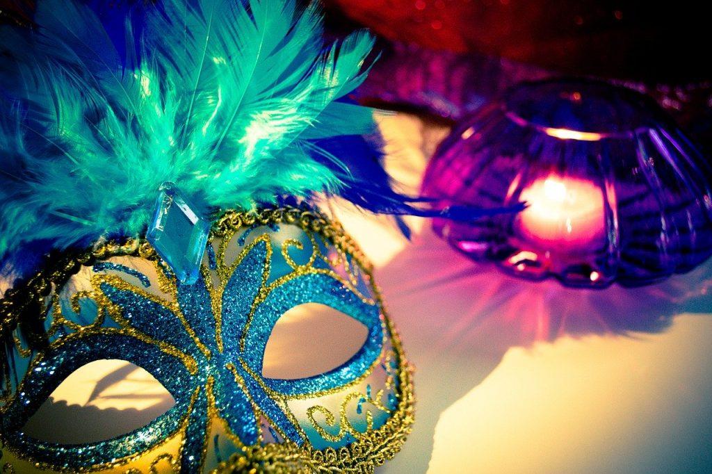 Máscara carnavalesca com detalhes em purpurina azul e amarela, e penas verdes, em cima de uma mesa ao lado de um vaso lilás com uma vela acesa dentro.