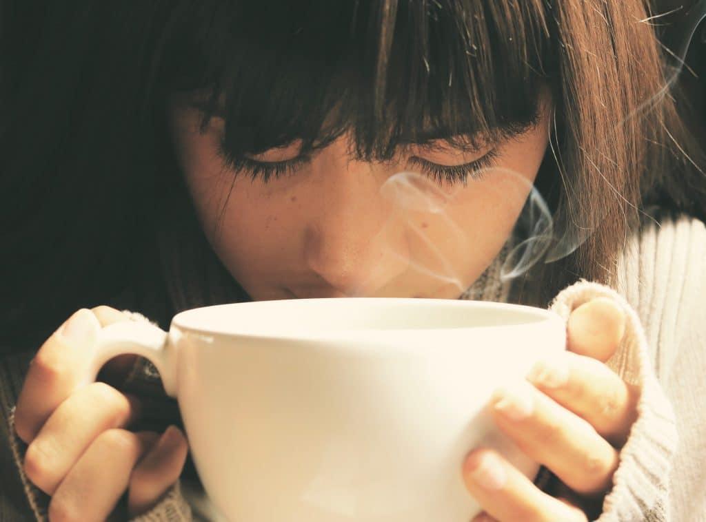 Imagem de uma mulher de cabelos castanhos. Ela está triste e segura entre as duas mãos uma xícara branca de porcelana cheia de chá.