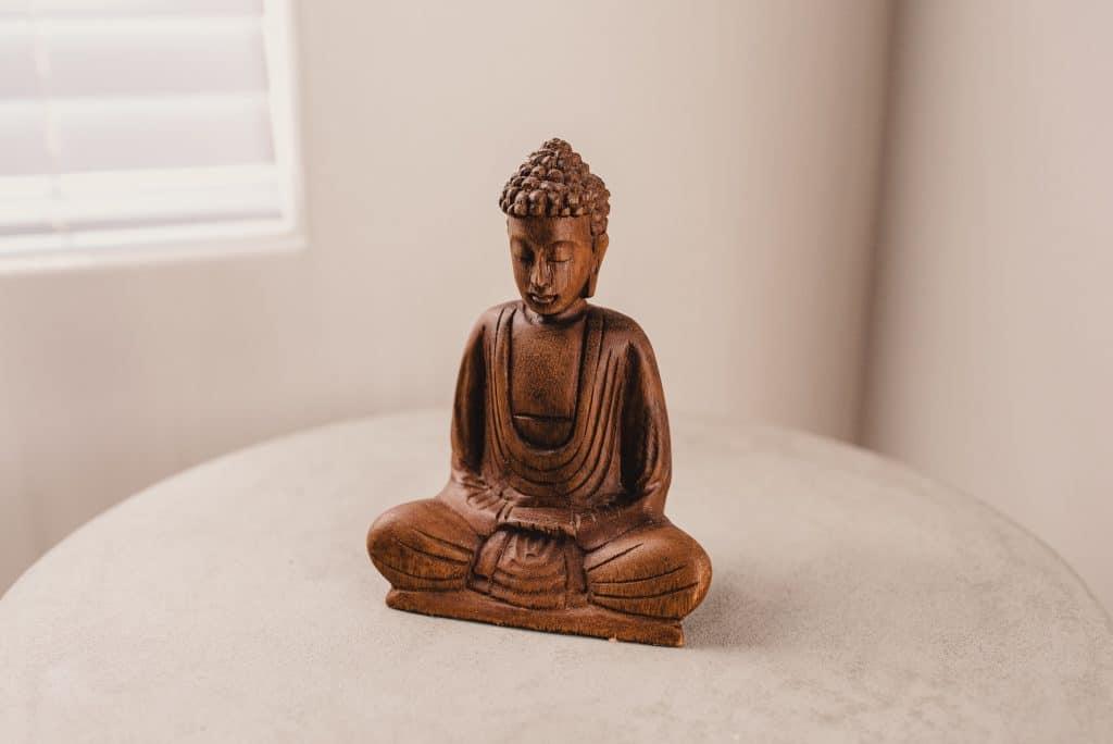 Estátua de cobre de um buda sentado em posição de meditação.