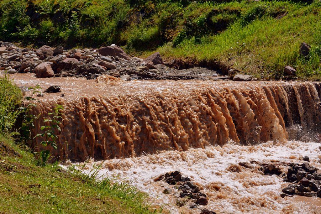 Água suja com barro, descendo em forma de cachoeira.