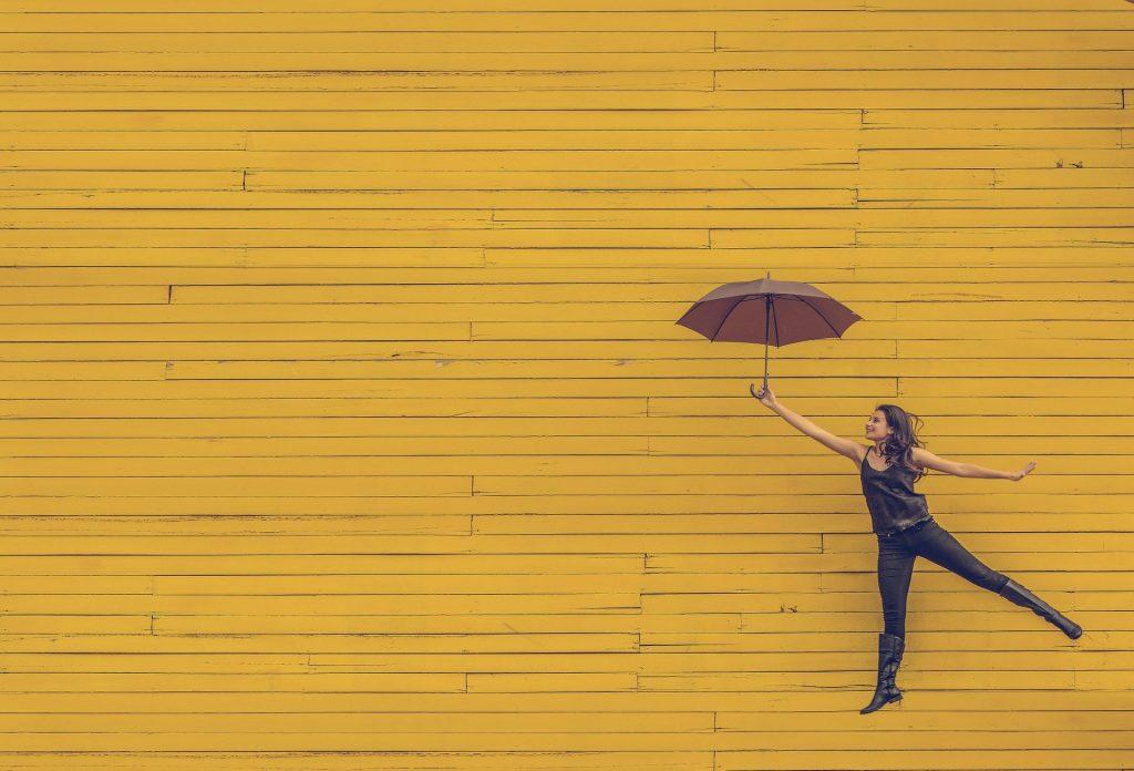 Imagem de uma mulher feliz vestindo uma roupa preta. Ela segura um guarda-chuva marrom. Ao fundo uma parede amarela.
