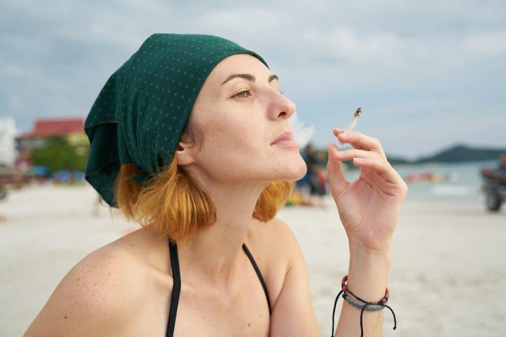 Imagem de uma mulher loira de cabelos curtos. Ela usa um lenço verde na cabeça, um biquini preto. Ela está na praia e fuma um cigarro.
