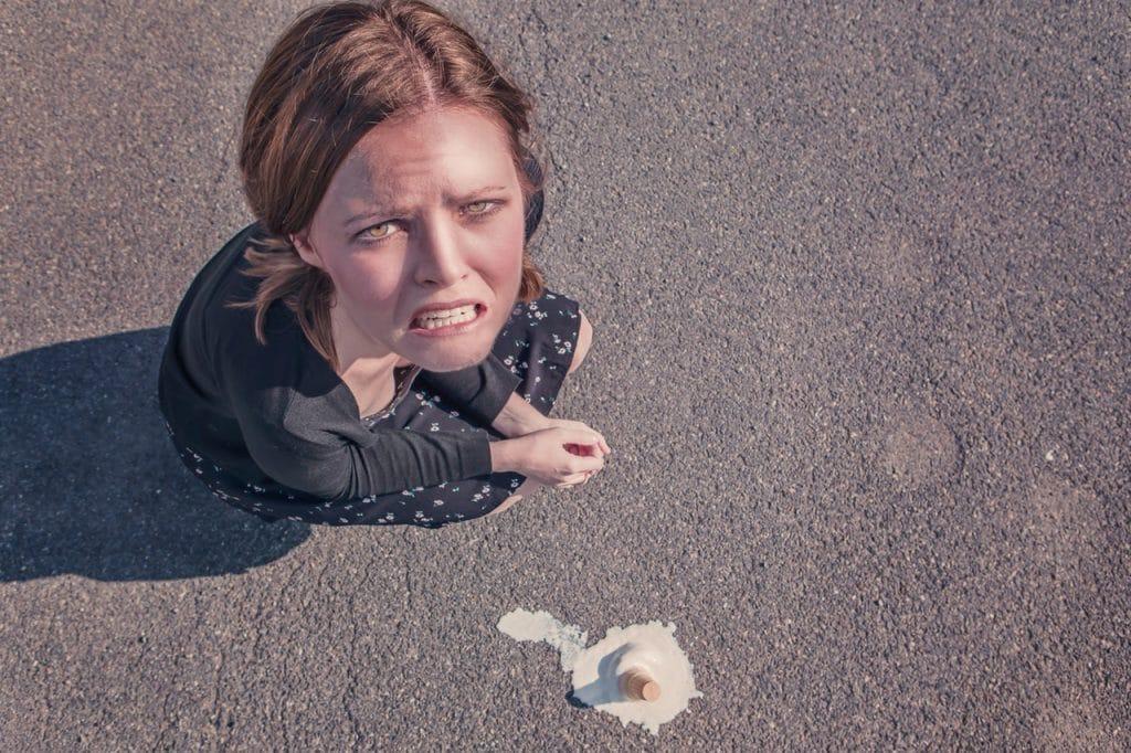 Mulher olhando para a câmera com cara de triste mostrando os dentes, e ao seu lado, no chão, um sorvete de casquinha que ela acaba de derrubar.
