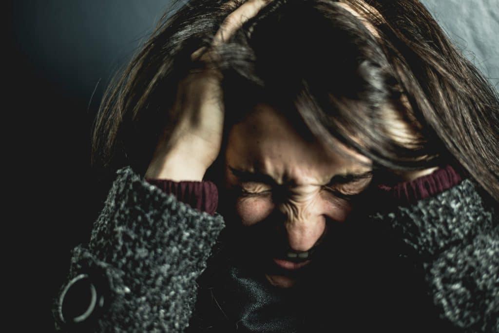 Mulher franzindo todo seu rosto, com os olhos fechados e a boca aberta como se estivesse gritando. Sua cabeça está baixa, e suas mãos estão em sua cabeça.