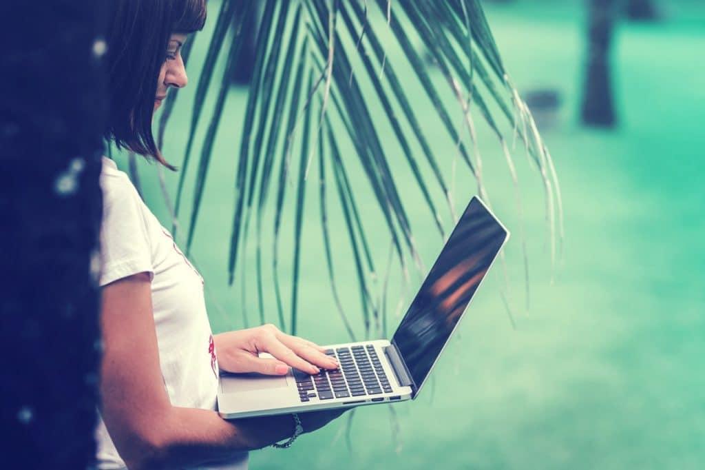 Mulher segurando notebook com a mão direita e digitando com a mão esquerda, embaixo de uma palmeira.