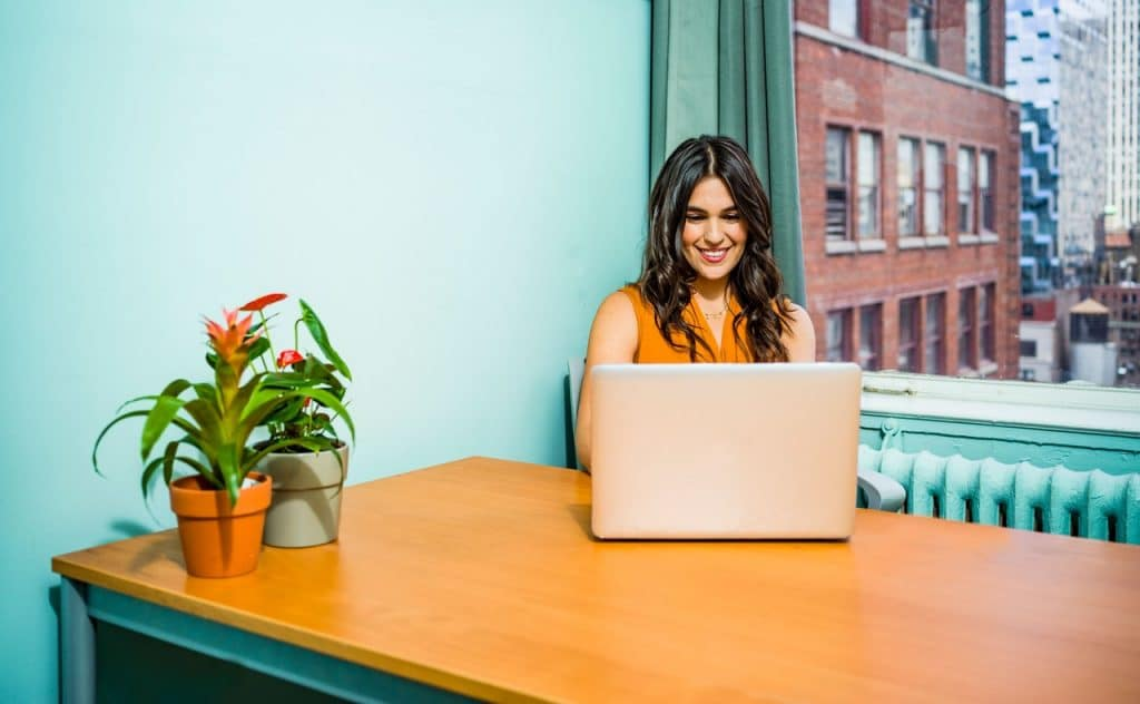 Mulher usando um notebook, em cima de uma mesa de escritório, com duas plantas em pequenos vasos. Ao fundo, uma janela com vista para uma cidade grande.