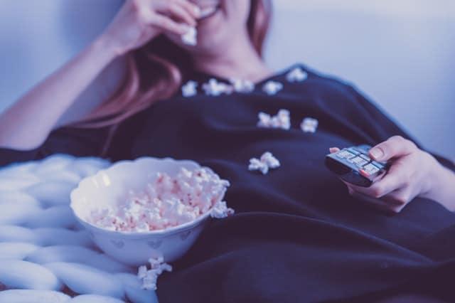Garota deitada na cama comendo pipoca segurando controle da TV e sorrindo