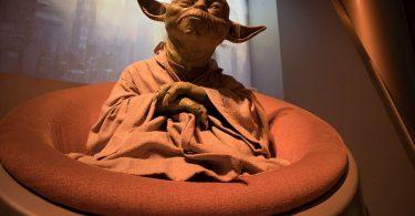 Yoda sentado em uma poltrona redonda, com suas mãos entrelaçadas e feição pensativa.