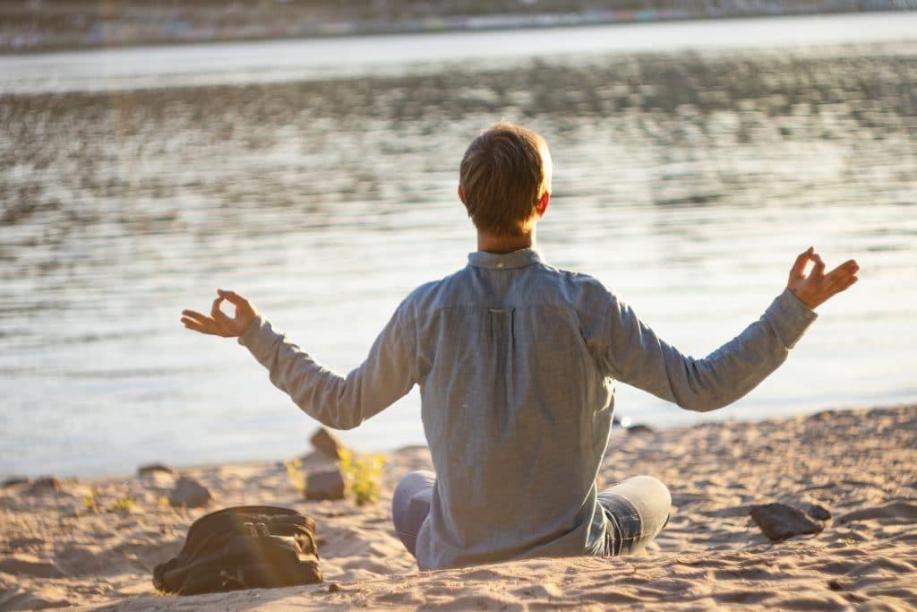 Imagem de um homem em posição de meditação. Ele está sentado sobre a areia de uma praia olhando para o mar.