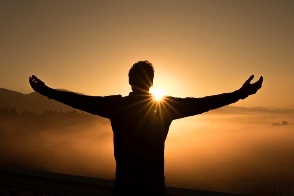 Silhueta de um homem, de costas, em cima de uma montanha, de braços abertos sob o pôr do sol.