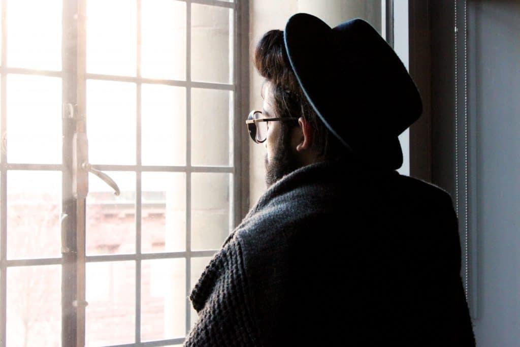 Homem olhando pela janela pensativo
