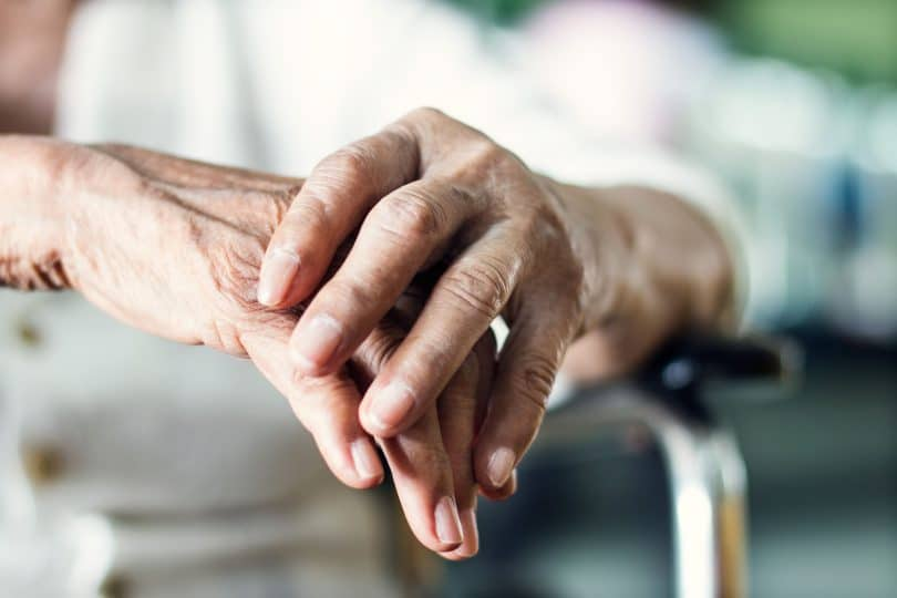 Senhora segurando suas mãos